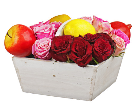 Flower arrangement of red roses and fruits in wooden basket isolated on white background. Closeup. Stock Photo - 23049495