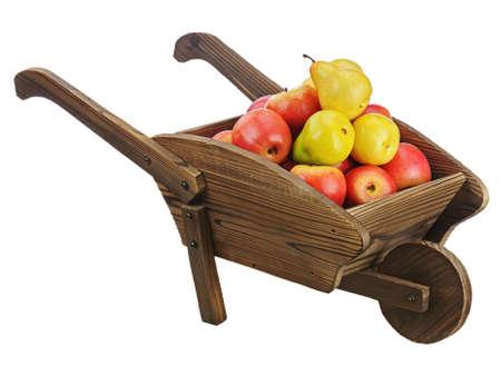 carretilla de mano: Manzanas rojas y peras en carretilla de madera aislada sobre fondo blanco. Primer plano.