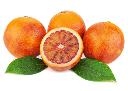 Ripe red blood oranges with cut and green leaves isolated on white background. Closeup.