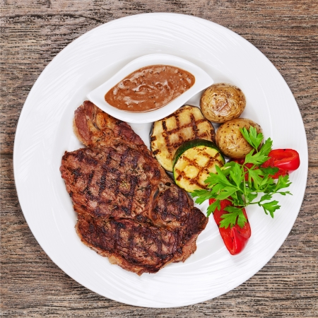 Grilled steaks, baked potatoes and vegetables on white plate on wooden background. photo