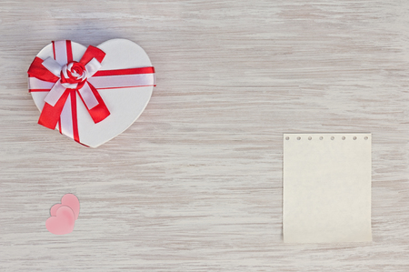 Valentine`s Day gift, heart and paper on wooden background. Closeup. photo