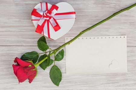 Valentine`s Day gift, rose and paper on wooden background. Closeup.