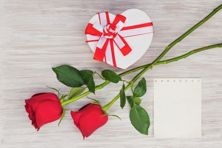 Valentine`s Day gift, roses and paper on wooden background. Closeup. photo