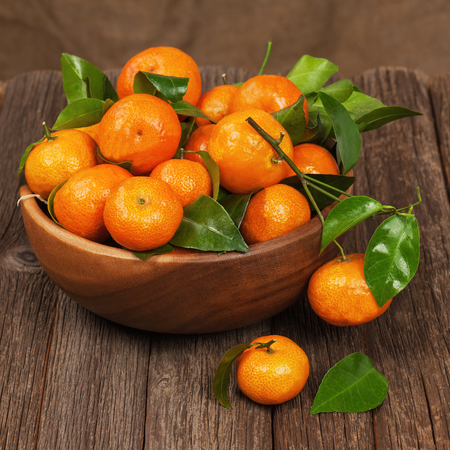 Fresh tangerines with leaves in bowl on wooden table. Closeup. photo