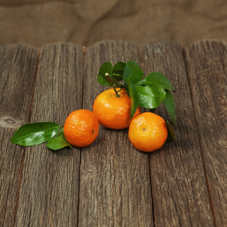 Fresh tangerines with leaves on a wooden table. Closeup. photo