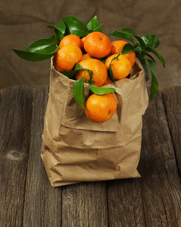 Fresh tangerines with leaves in recycle paper bag on wooden table. Closeup. photo