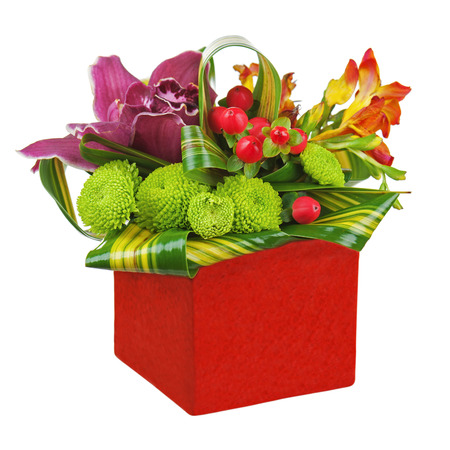Bouquet from orchids and lilies in red vase isolated on white background  Closeup  photo