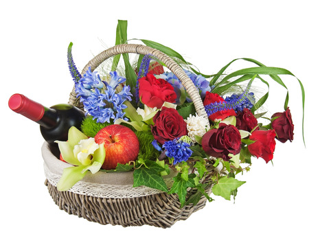 Flower arrangement of roses, orchids, fruits and bottle of wine isolated on white background  photo