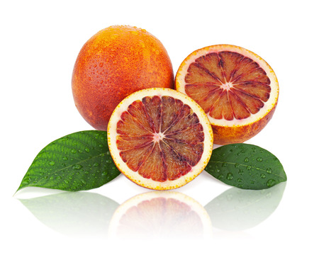 Blood oranges with cut and green leaves isolated on white background. Closeup. photo