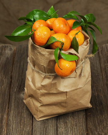Fresh tangerines with leaves in recycle paper bag on wooden table. photo