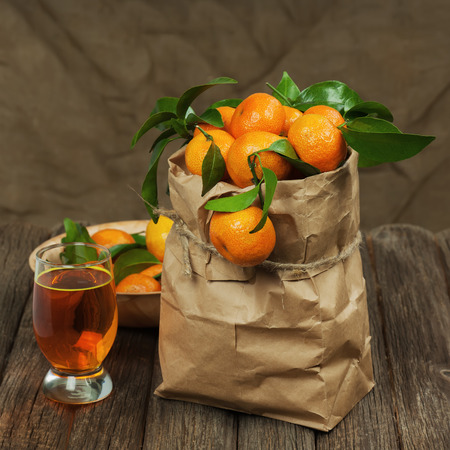 Fresh tangerines in recycle paper bag and glass of juice on wooden table. Closeup. photo