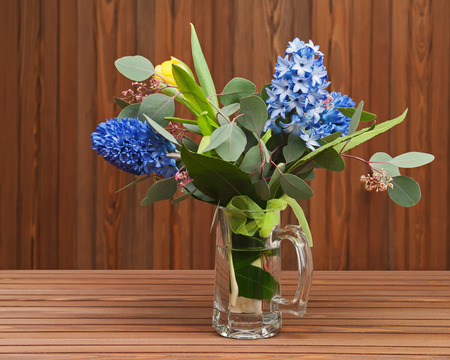 Bouquet from tulips and hyacinths in glass vase on wooden background. photo