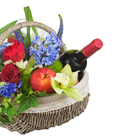 Flower arrangement of roses, orchids, fruits and bottle of wine isolated on white background. photo