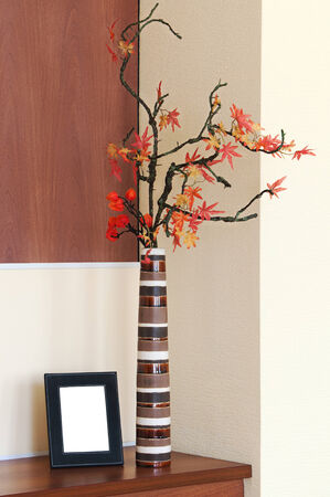 Autumn arrangement in a vase on the table and photoframe with place for your foto. photo