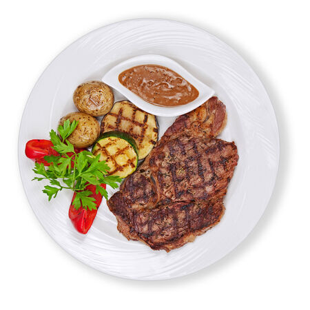 Grilled steak, baked potatoes and vegetables on white plate isolated on white background. photo