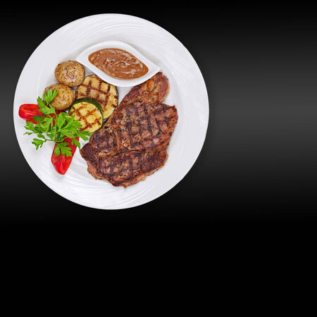 Grilled steak, baked potatoes and vegetables on white plate on black background. photo