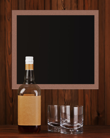 Two glasses with ice for whiskey and bottle on dark wooden background. photo