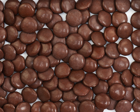 dragee: Dark brown dragee in chocolate covered. Whole background. Stock Photo