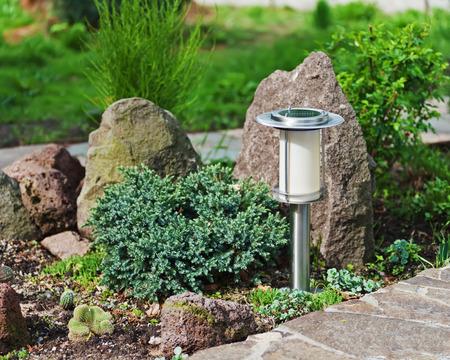Solar-powered lamp on garden background. Selective focus.