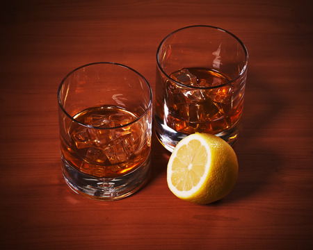 highball: Highball whiskey glass with ice and lemon on wooden background. Close up. Stock Photo
