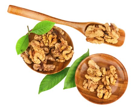 macr: Handful of walnuts in wooden bowls, scoop and green leaves isolated on white background  Closeup