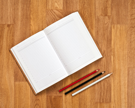 Blank notepad with office supplies on wooden table. Above view. photo