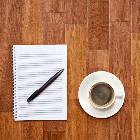Blank notepad with office supplies and cup of coffee on wooden table. Above view. photo