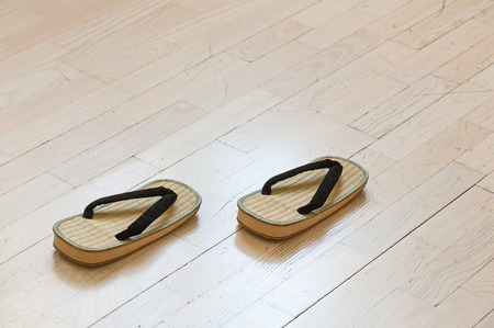 ryokan: Pair of Traditional Japanese Sandals on Old Wooden Floor. Selective Focus.
