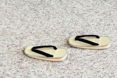 Pair of Traditional Japanese Sandals on Carpet Floor. Selective Focus. photo