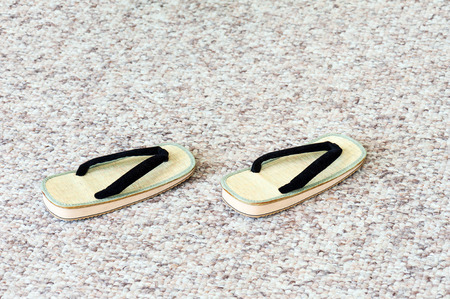 ryokan: Pair of Traditional Japanese Sandals on Carpet Floor. Selective Focus.