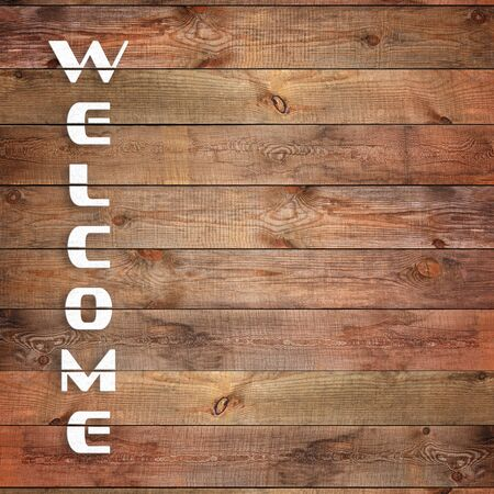 surface closeup: Vintage WELCOME sign on natural wooden surface. Closeup.