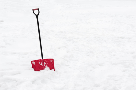 Red snow shovel standing in snow. Winter concept.