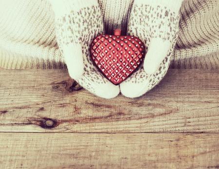 ragazza innamorata: Le mani di donna in light leggings a maglia sono in possesso di cuore rosso su sfondo di legno. Inverno, giorno di San Valentino e concetto di Natale.