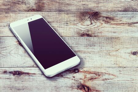 communicator: Realistic mobile phone with black screen and shadows on wooden background. Highly detailed illustration. Stock Photo