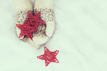 Woman hands in light teal knitted mittens are holding red stars on snow background. Winter and Christmas concept. Stock Photo