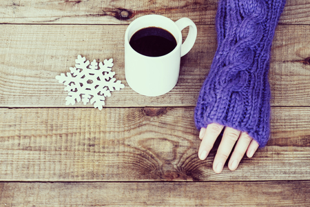 sweater girl: Woman hand in teal glove, mug with hot coffee or cocoa and snowflake on wooden background.  Winter and Christmas concept.