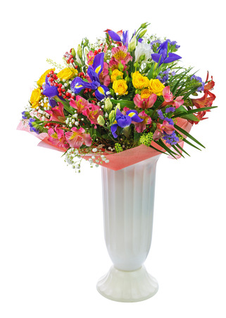 Delicate beautiful bouquet of roses, iris, alstroemeria, nerine and other flowers with colored packaging in vase solated on white background.