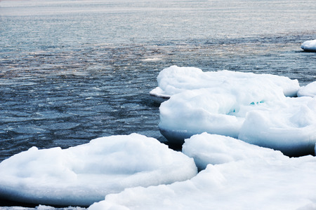 Natural sea ice blocks breaking up against shore and ice during freezing winter weather. Arctic aquatic nature.