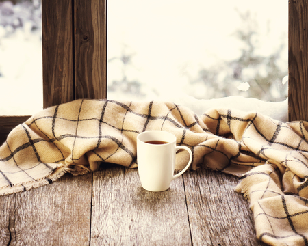 wooden window: White cup of coffee or tea and woolen plaid located on stylized wooden window sill. Winter concept of comfort and relaxation.  Photo with retro filter effect.