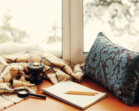 Open notepad, magnifier glass, pillow, candle, pencils and beige warm plaid located on stylized wooden windowsill. Winter concept of comfort and relaxation.  Photo with retro filter effect.