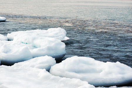 breaking up: Natural sea ice blocks breaking up against shore and ice during freezing winter weather. Arctic aquatic nature.
