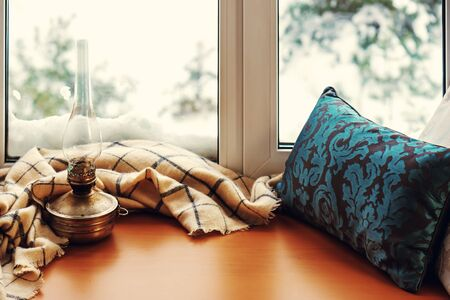 frost winter: Beige woolen scarf and old lamp located on stylized wooden window sill. Winter concept of comfort and relaxation. Photo with retro filter effect.