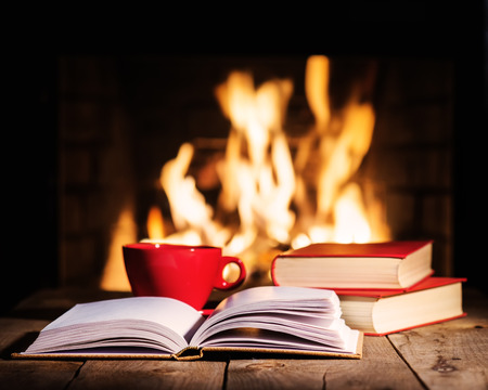 Red cup of coffee or tea and old books on wooden table near  fireplace. Winter and Christmas holiday concept.