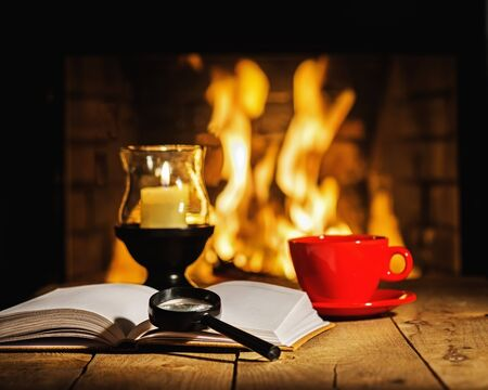 tea candle: Red cup of coffee or tea, candle in lamp, magnifier glass and old book on wooden table near fireplace. Winter and Christmas holiday concept.