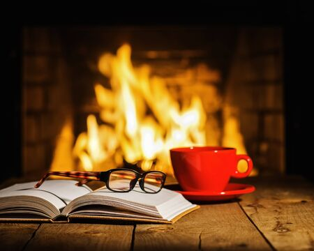 Red cup of coffee or tea, glasses and old book on wooden table near fireplace. Winter and Christmas holiday concept. Stok Fotoğraf