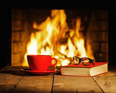 llamas de fuego: rojo taza de caf� o t�, gafas y viejo libro sobre la mesa de madera cerca de la chimenea. Invierno y concepto de vacaciones de Navidad.