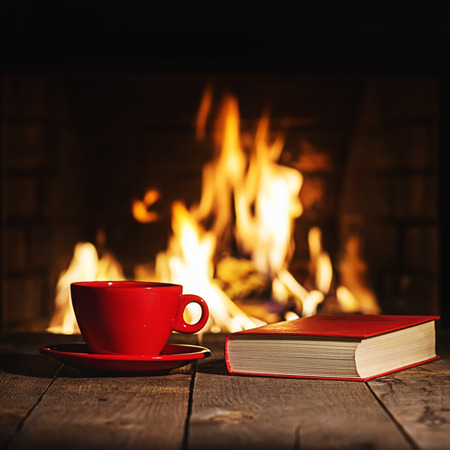 fireplace home: Red cup of coffee or tea and old book on wooden table near  fireplace. Winter and Christmas holiday concept.