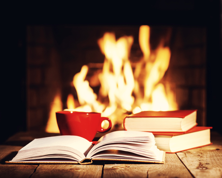 Red cup of coffee or tea and old books on wooden table near  fireplace. Winter and Christmas holiday concept. Photo with retro filter effect.