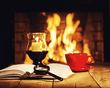tea lamp: Red cup of coffee or tea, candle in lamp, magnifier glass and old book on wooden table near fireplace. Winter and Christmas holiday concept. Photo with retro filter effect.