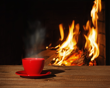 hearth and home: Red cup of tea or coffee near fireplace on wooden table. Winter and Christmas holiday concept.